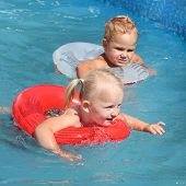 Two children swimming in a life ring.