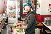 Hotdog - friendly chef preparing fresh ingredients in a fast food snack bar