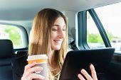 Junge geschäftsfrau unterwegs im Taxi, sie halten Tasse Kaffee und einem Tablettcomputer