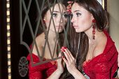 Toung girl in the red dress looks in the mirror