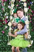 Smiling father with baby and little girl with shamrock on head on swing in garden next to verdant fe