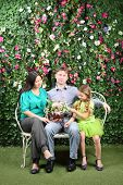 Family of three sit on white bench with bunch of flowers in garden near verdant hedge.