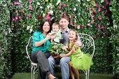 Family of four with bunch of flowers sit on bench in garden near verdant hedge.