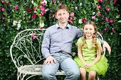 Happy father and daughter sit on white retro bench near verdant hedge.