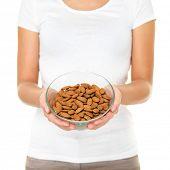 Tuercas de almendras - tazón de almendra cruda de mujer mostrando. Concepto de comida saludable en estudio con las manos levantar el tazón de fuente