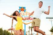 Las Vegas Sign. Happy couple jumping. People having fun in front of Welcome to Fabulous Las Vegas si