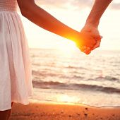 Love - romantic couple holding hands, beach sunset. Lovers or newlywed married young couple in romance on beautiful sunset at beach. Young woman and man in love walking hand in hand on beach.