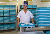 stock photo of porter  - Portrait of middle aged porter with plastic trays in hospital kitchen - JPG