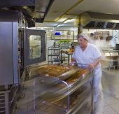 Female kitchen porter pushes a trolley of pastries