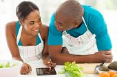 lovely young african american couple searching for a recipe on tablet computer
