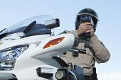 Low angle view of middle aged policeman monitoring speed through radar against sky