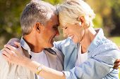 stock photo of hug  - loving middle aged couple hugging with eyes closed closeup portrait - JPG