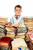 A boy sitting on a pile of books and reading a book. Education. Isolated over white.