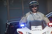 Confident middle aged policeman wearing helmet while sitting on motorbike