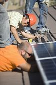 Male engineers working on solar panel at rooftop