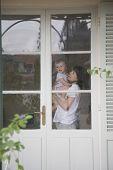 Side view of happy mother carrying baby in front of door