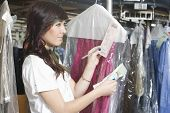 Side view of young woman checking receipts of dry clean clothes in laundry