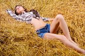 Chica joven tumbado en el pajar