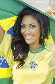 Beautiful football fan soccer in Brazilian color holding Brazil flag,