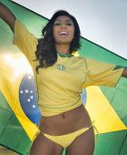 Beautiful happy smiling young woman holding Brazil flag wearing soccer top and bikini bottom