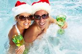 Happy christmas santa couple in hot tub. Vacation.