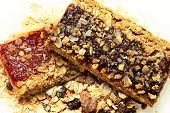 Blueberry and Strawberry Granola Bars stacked in pile of oats and nuts.