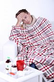 Guy wrapped in plaid sitting on sofa is ill