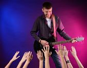picture of adoration  - Guitarist singing on stage at a rock concert for his adoring fans - JPG