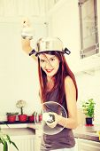 Kitchen Knight - young beautiful caucasian woman in kitchen with pot on her head (as helmet) and hoh