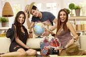 Happy young roommates planning summer holiday, having globe, smiling.