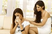 Young woman consoling crying friend at home.