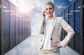 Cheerful elegant businesswoman on the phone against server hallway in the sky