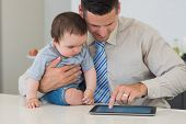 Young businessman using digital tablet while holding baby boy at counter in house