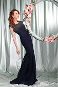 Beautiful  redheaded girl in evening dress  with the hoop with pink flowers