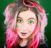 funny girl with crazy make-up over green background