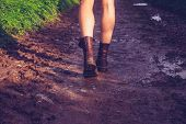 Young Woman Walking Along Muddy Trail