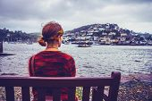pic of dartmouth  - Woman on bench admiring view of seaside town - JPG