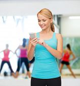 sport, excercise, technology, internet and healthcare - sporty woman with smartphone