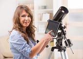 Beautiful woman with astronomical telescope standing near a window and checking something about stars and planets on the tablet