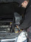 Auto mechanic measuring car battery voltage using multimeter