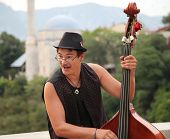MOSTAR, BOSNIA AND HERZEGOVINA - AUGUST 9, 2012: Street musician plays double bass. The streets of M