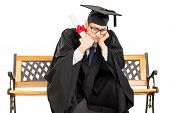 Worried student in graduation gown seated on bench holding diploma isolated on white background