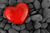 Red heart on a background of river stones.