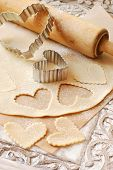 Heart shaped cookie cutters with dough and vintage rolling pin (dusted with flour) on rustic wood tr
