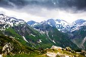 Green And Snowy Mountains With Dark Storm Clouds Above