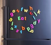 Word Eat spelled out using colorful magnetic letters on refrigerator