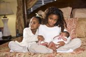 Ten and four year old sisters holding their newborn sibling