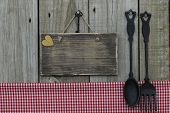 Blank wood sign with cast iron spoon and fork and checkered tablecloth