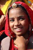 PUSHKAR, INDIA - NOVEMBER 21 2012: Portrait of smiling Indian girl in colorful ethnic attire at Pushkar camel fair