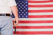 man standing in front of the stars and stripes holding a handgun